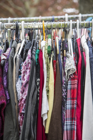 specific clothing: clothes on a rack in a flea market .