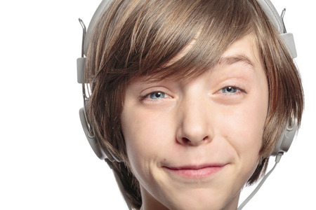 male teenager with headphones hurts the music, isolated on white. photo