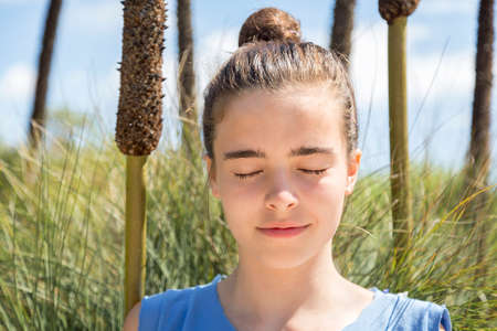 teenager girl meditates in front of a reed field. photo