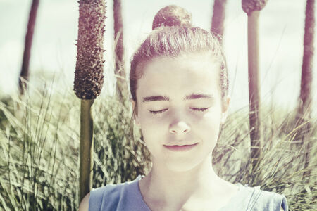 vintage version of a teenager girl meditates in front of a reed field. photo
