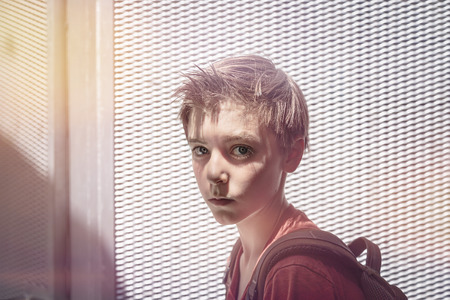 portrait of a teenager boy with rucksack and extreme light in front of a metal grid pattern