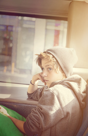 portrait of a teenager boy with toque, sitting in a bus. photo