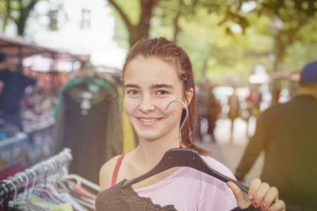 specific clothing: smiling woman on a flea market is holding a clothes hanger.