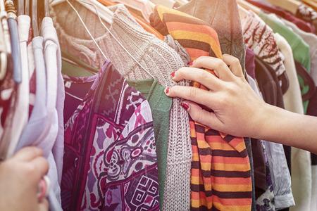 ropa colgada: Primer plano de una mano, mirando en un mercado de pulgas para la ropa.
