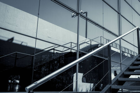 detail of a glass facade with reflection and handrail photo