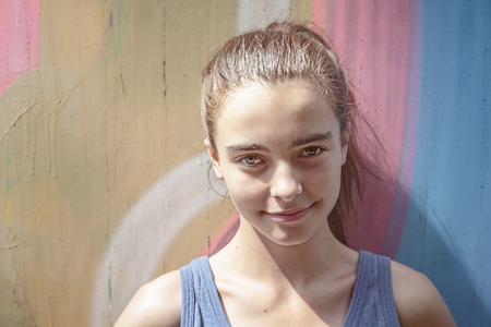 toned image: toned image, smiling girl in front of a graffiti