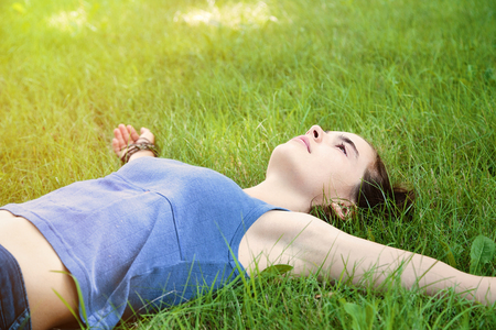stretched out: teenage girl laying on a meadow with stretched out arms