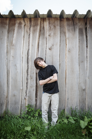 oblique standing teenage boy in front of a wooden wall photo