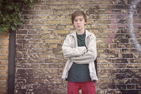 portrait of a serious teenage boy with crossed arms photo
