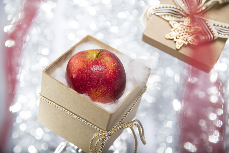 open christmas gift box with an apple, ribbon and bow photo