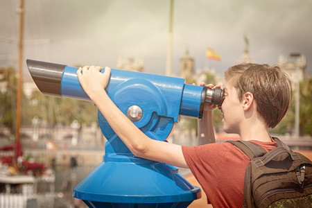 monocular: teenage boy with rucksack looking through a sightseeing monocular Stock Photo