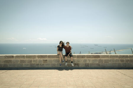 mutually: Castell de Montbejuic Barcelona, sister and brother sitting on a wall Stock Photo