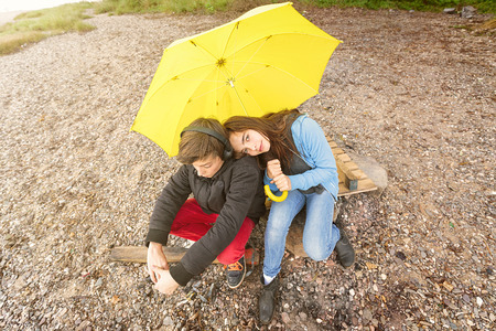 mutually: brother and sister with yellow umbrella sitting on a dirty beach