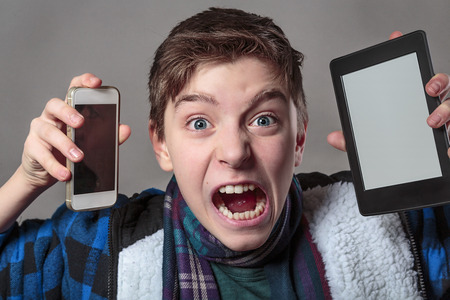 teenager gets crazy with digital media, gray background for fast isolating