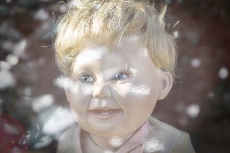 male plastic doll head shot through a mirroring window, with bokeh