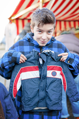 funny teenage boy on a flea market is trying too small dresses Stockfoto