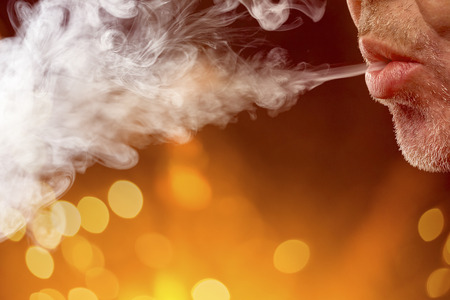 male mouth is blowing smoke out, with bokeh background