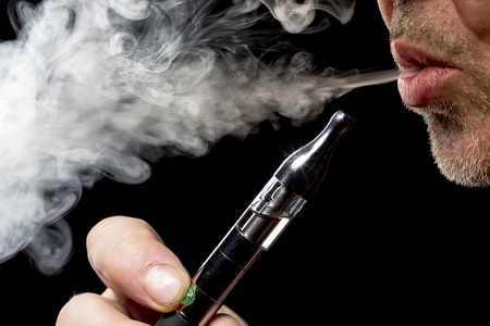close up portrait of a man smoking an e-cigarette Фото со стока