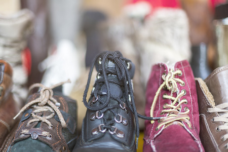 a row of old shoes on a flea market, with backlit