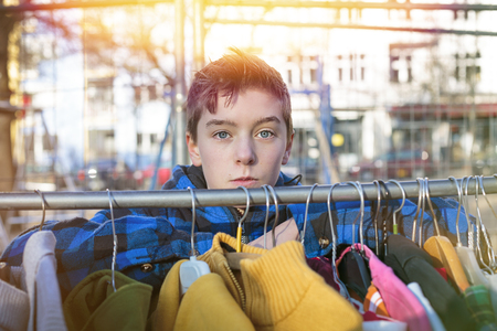 specific clothing: portrait of a teenage boy behind a clothes rail on a flea market Stock Photo