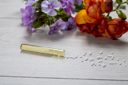 globules: small glass tube with homeopathy globules  and flowers