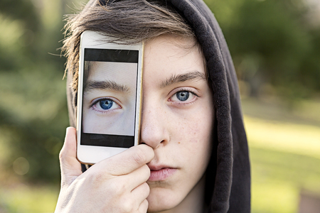 compensatory: virtual realty teenage boy holding a smart phone in front of his face Stock Photo
