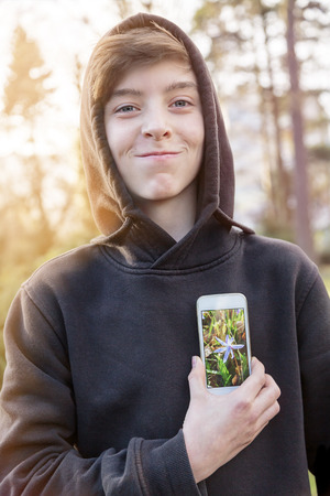 compensatory: virtual realty teenage boy holding a smart phone in front of his heart Stock Photo