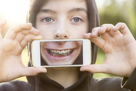 gar�on souriant: immobilier virtuel, adolescent tenant un t�l�phone intelligent en face de son visage Banque d'images