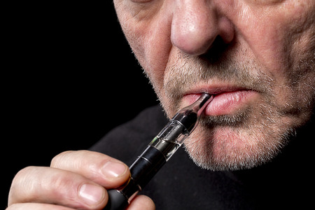 close up portrait of a man smoking an e-cigarette Stock Photo