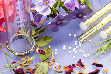 homeopatia: tubos de vidrio pequeños con glóbulos de homeopatía, la jeringa y flores