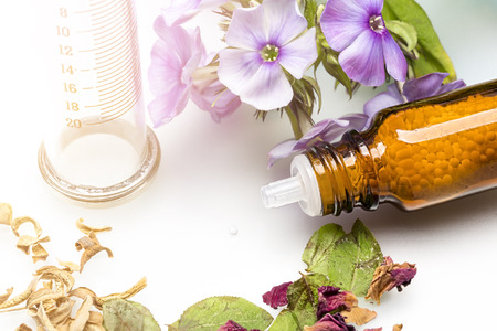 bottle with homeopathy globules, syringe and flowers 写真素材