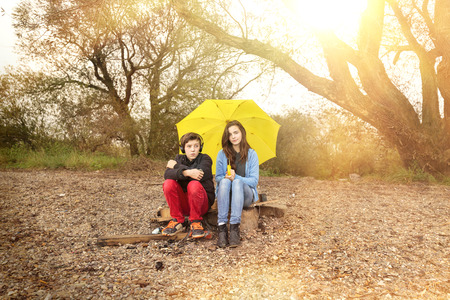 mutually: two teenager with umbrella sitting on a dirty beach with sun in background