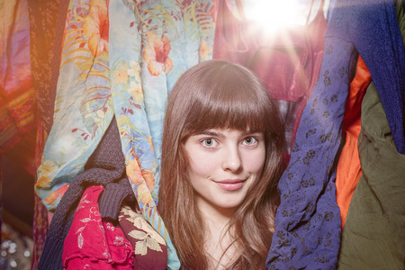 clothing rack: portrait of a beautiful teenage girl and her wardrobe, with bokeh Stock Photo