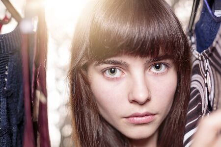 specific clothing: portrait of a beautiful teenage girl and her wardrobe, with bokeh Stock Photo