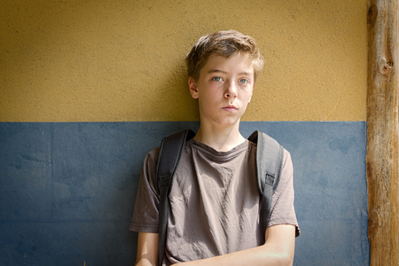 portrait of a sitting sad teenage boy