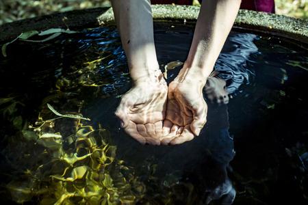 カップの手で井戸から水を保持しています。