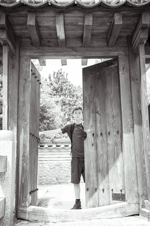 ancient japanese: teenage boy is standing at a ancient japanese gate Stock Photo
