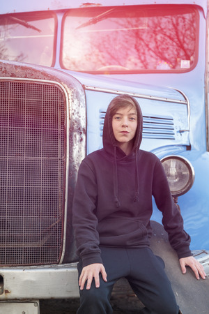 cool guy: teenage boy with skateboard sitting on an old truck