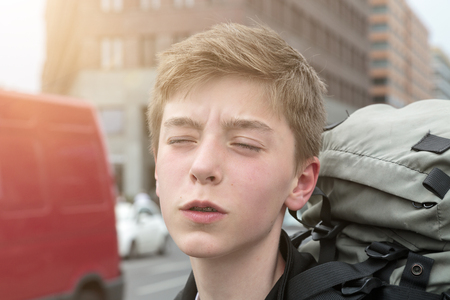 beautiful boys: portrait of a suffering teenage boy with heavy backpack
