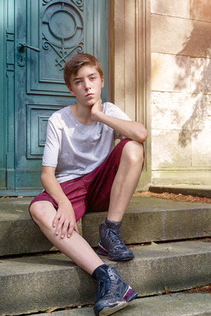 cool guy: portrait of a sitting teenage boy in summer Stock Photo