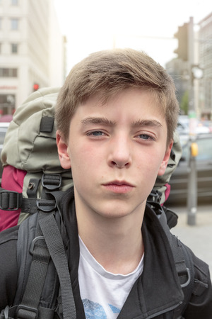 portrait of a teenage boy with heavy backpack