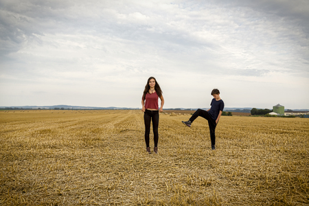 mutually: tow teenager playing on a harvested field