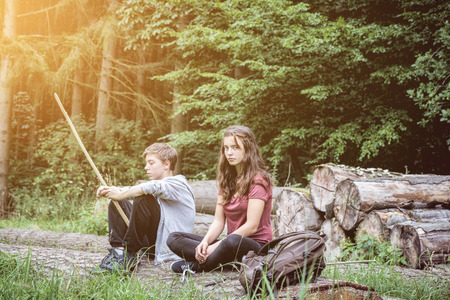 mutually: brother and sister resting on a tree trunk
