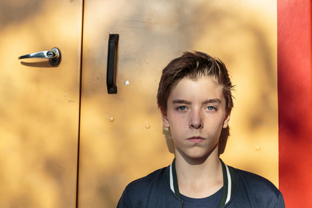 cool guy: portrait of a teenage boy in front of a yellow door