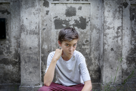 cool guy: portrait of a crouching teenage boy Stock Photo