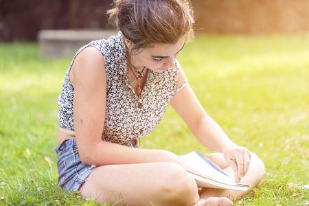 student writing: teenage girl making here homework sitting in a garden