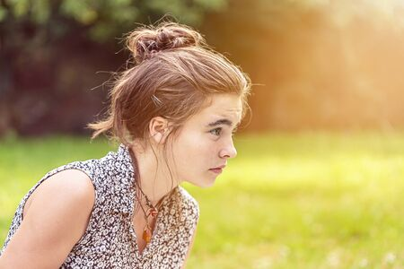 teenage girl looking concentrated, in profile