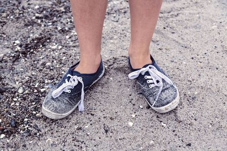two legs with old dirty blue shoes at the beach Stock Photo
