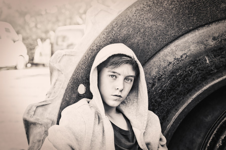 model portrait: portrait of a teenage boy leaning against a huge tire Stock Photo