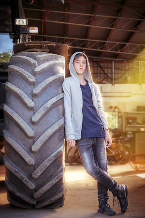 lean machine: portrait of a teenage boy leaning against a huge tire Stock Photo